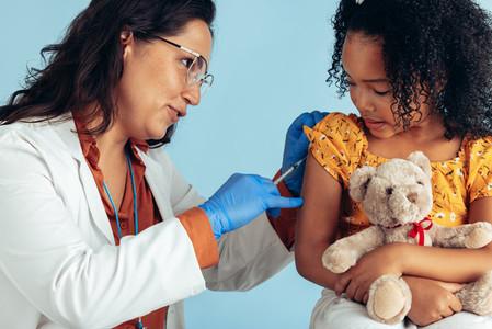 Doctor giving flu shot to a girl