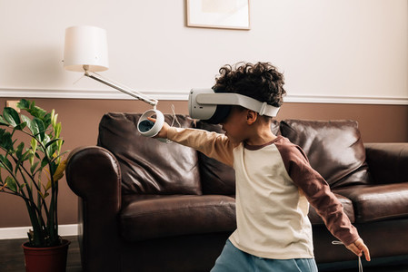 Little boy in VR goggles in living room  Kid enjoying virtual reality game using a controller