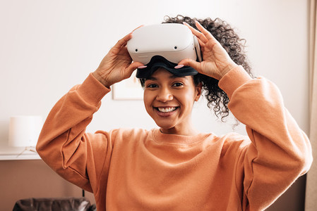 Happy mixed race woman looking at camera wearing VR goggles