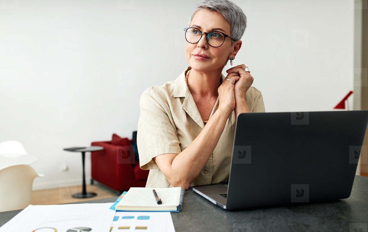 Thoughtful mature woman wearing eyeglasses sitting at a desk at home looking away
