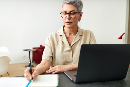 Mature woman writing on a note pad while using laptop computer at home