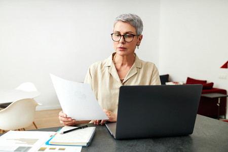 Mature woman with documents using laptop at home