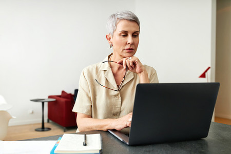Mature adult female holding glasses typing on a laptop at home