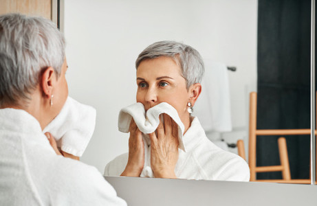 Mature adult woman wiping her face after morning routine in the bathroom