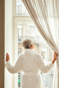 Rear view of a senior woman in bathrobe opening curtains in the morning