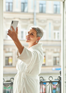 Senior woman wearing bathrobe holding a smartphone at hotel room