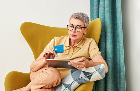 Mature woman in glasses sitting on armchair in living room shopping online