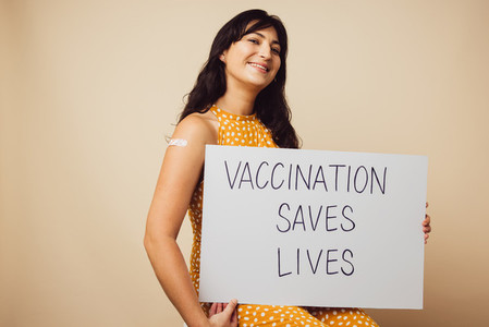 Beautiful woman holding vaccination saves lives signboard