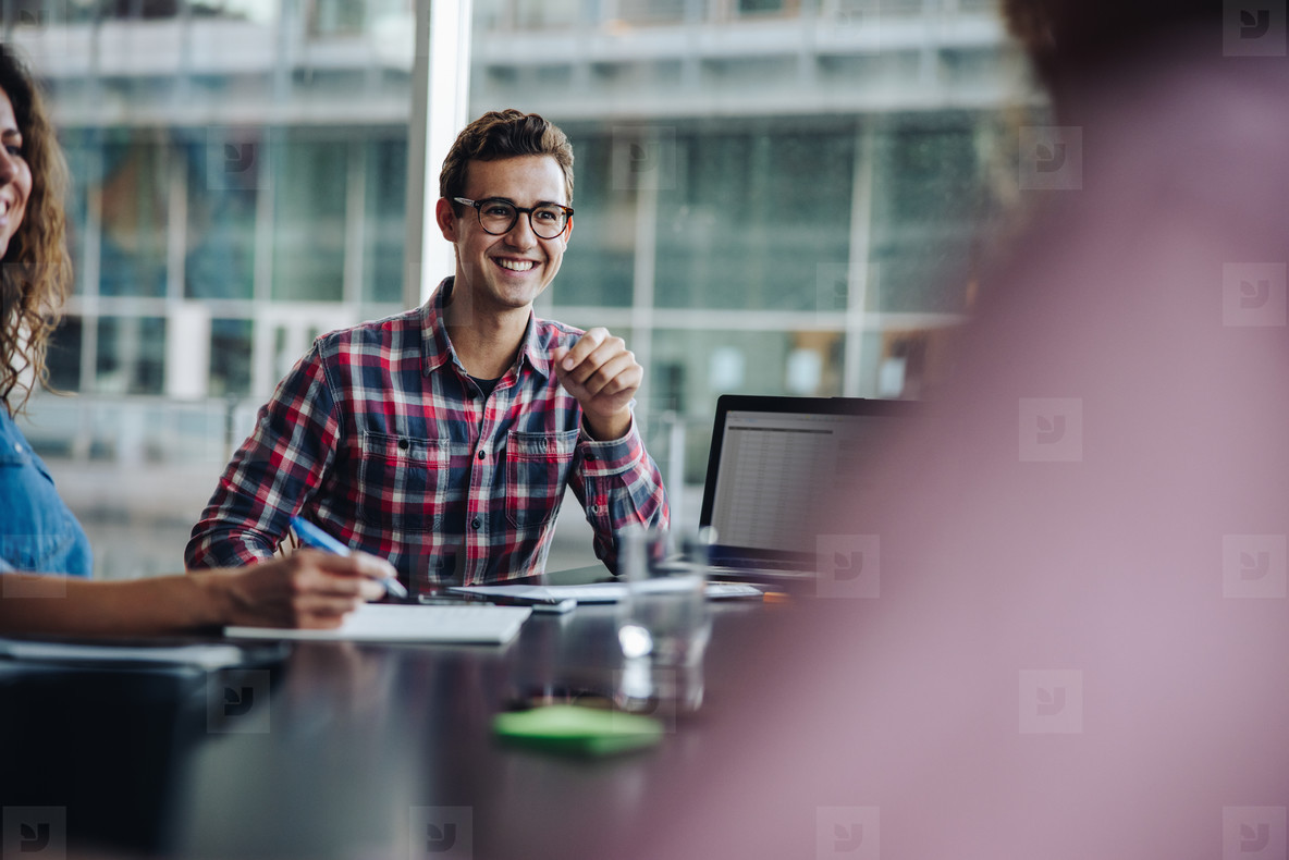 Smiling young man sitting in boardroom meeting