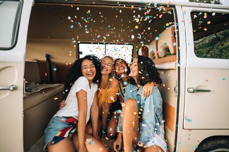 Group of happy women sitting in a camper van door under confetti  Friends having fun on a road trip