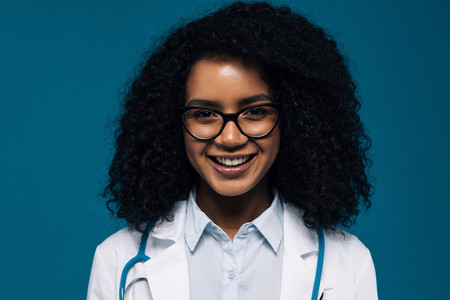 Close up of a beautiful smiling doctor in glasses looking at camera over blue background