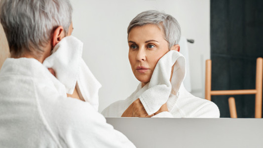 Mature woman with short grey hair looking at her reflection in bathroom mirror while wiping cheek