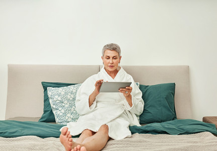 Adult female in bathrobe lying on a bed using a digital tablet