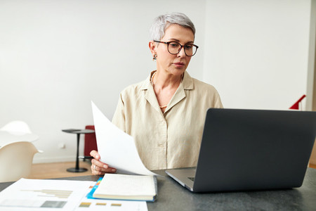 Mature woman with documents using laptop at desk in living room