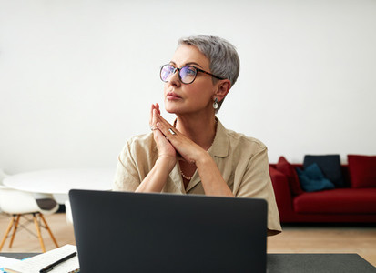 Stylish mature woman in glasses sitting at desk looking away