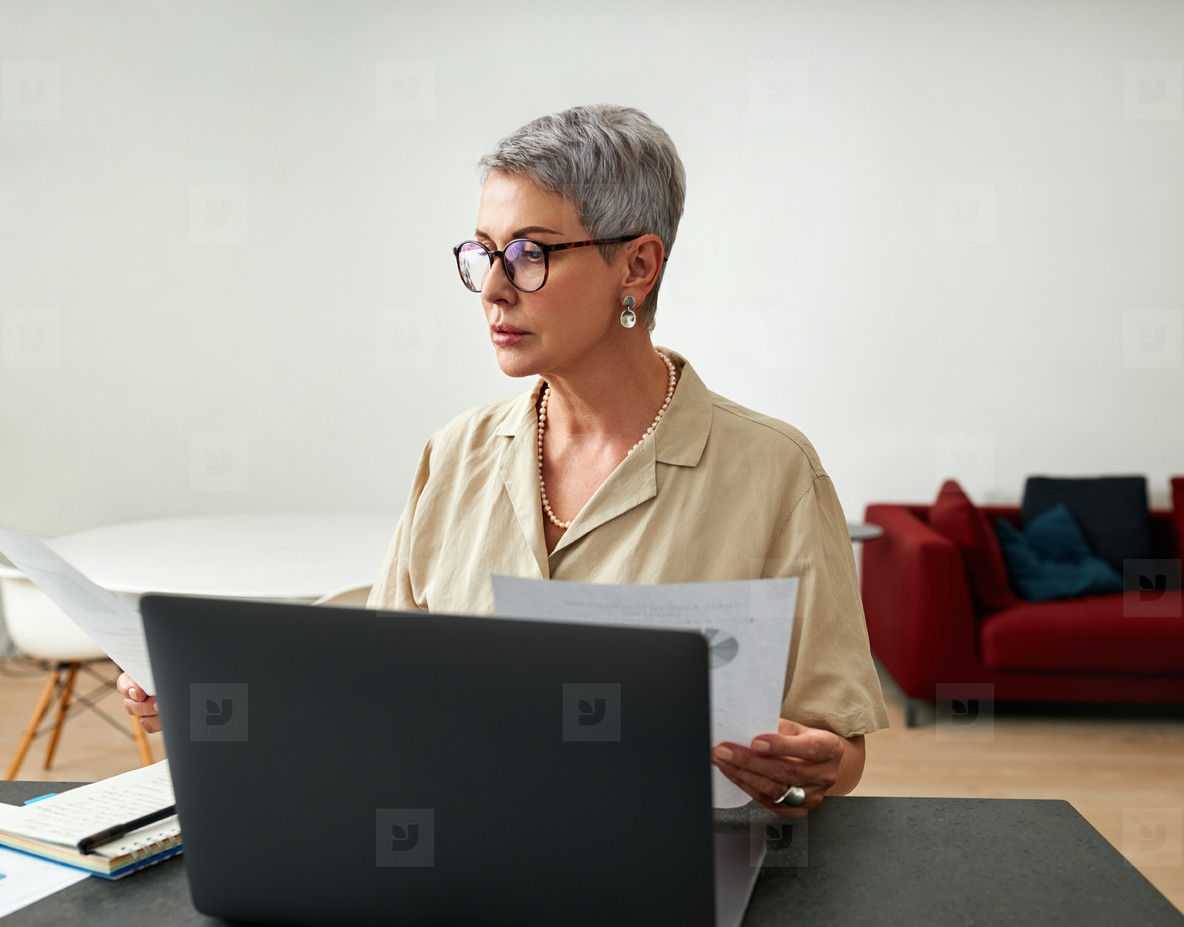 Mature woman sitting at a desk in a living room holding documents