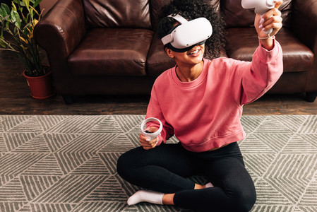 Smiling woman in living room using VR set  Young female in comfy clothes playing video games while sitting on the floor