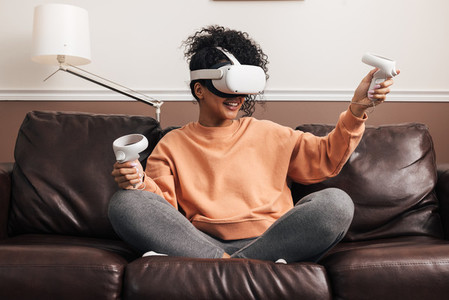 Woman with joysticks and VR goggles playing video games on a sofa