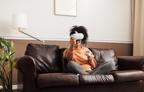 Woman in casual clothes relaxing at home Mixed race female having fun while playing video games with VR set
