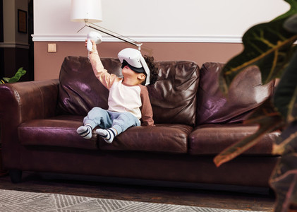 Little boy in comfy clothes using VR set while sitting on a sofa  Kid raising hand with a joystick