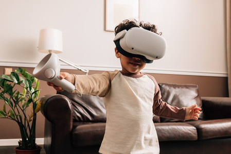 Little boy wearing VR glasses and holding a controller while standing in living room