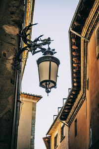 forge dragon holding a street lamp in a city near barcelona