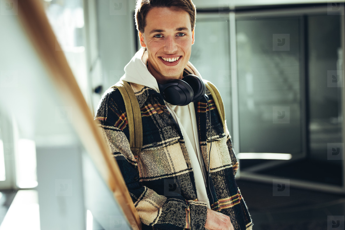 Young man smiling at camera at college staircase