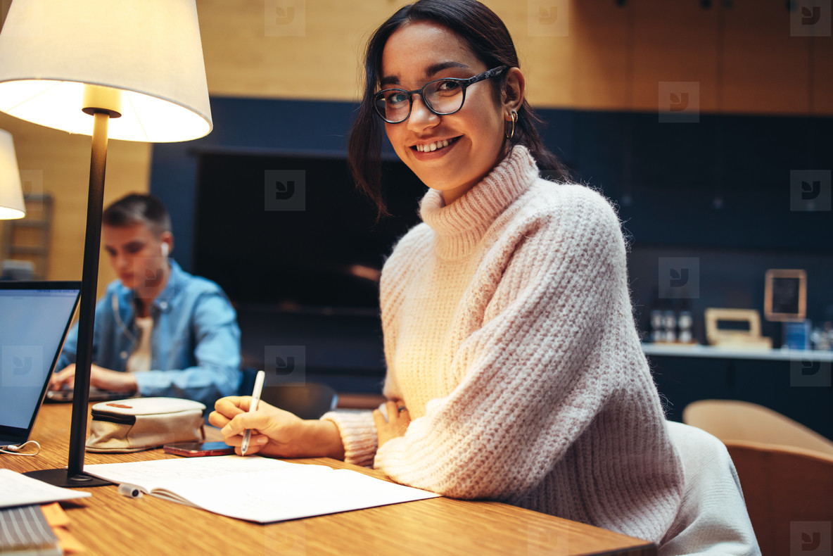 Smiling student studying in university library