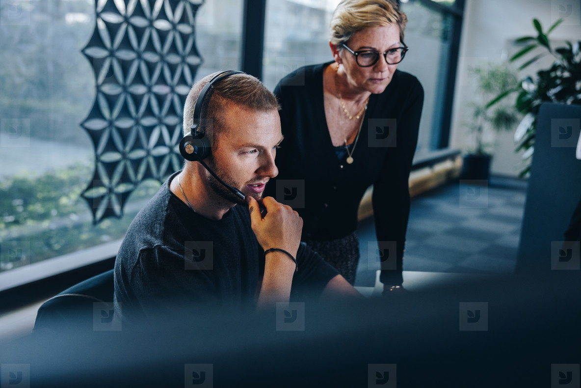 Businessman with headset working at his desk with manager