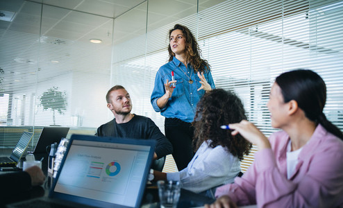 Businesswoman sharing new ideas with team in presentation