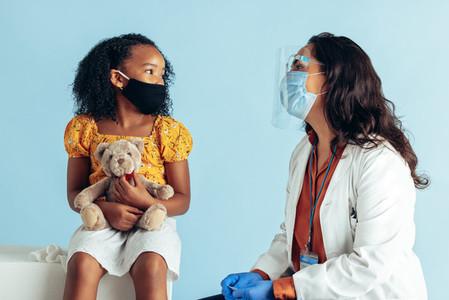 Doctor examining girl during pandemic