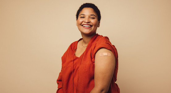 Woman showing her arm after receiving a vaccine