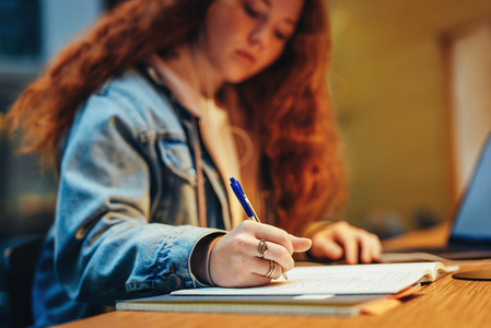 Young student writing notes at library desk