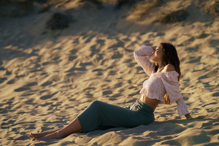 Attractive woman sitting on the sand of the beach