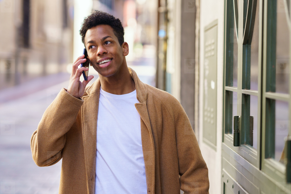 Young black man talking on the phone while walking down the street
