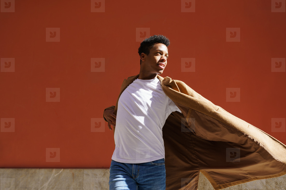 Young black man dancing on red urban wall