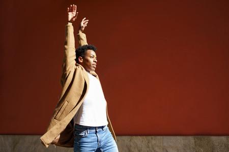 Young Cuban man dancing on red urban wall