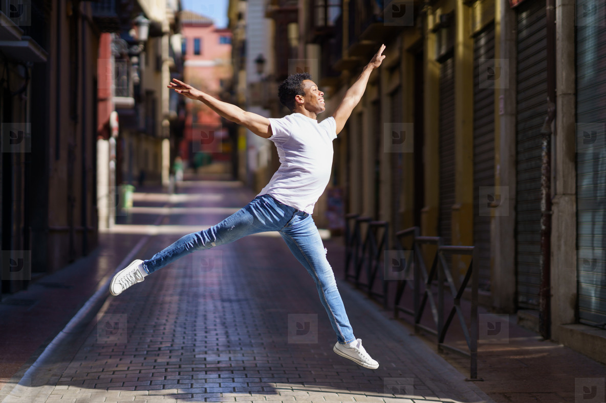 Happy black guy doing an acrobatic jump in the middle of the street