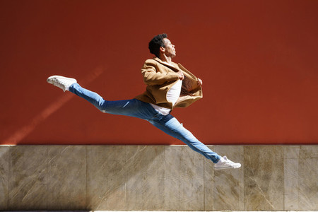 Black athletic man doing an acrobatic jump outdoors