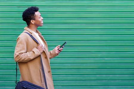 Cuban young man looking forward using his smartphone near green blinds