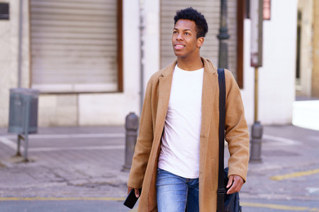 Young black man walking down the street carrying a briefcase and a smartphone in his hand