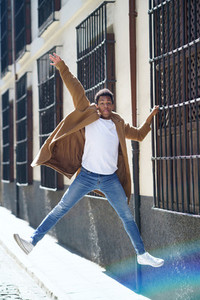 Young black man jumping holding on to a window grille in the street