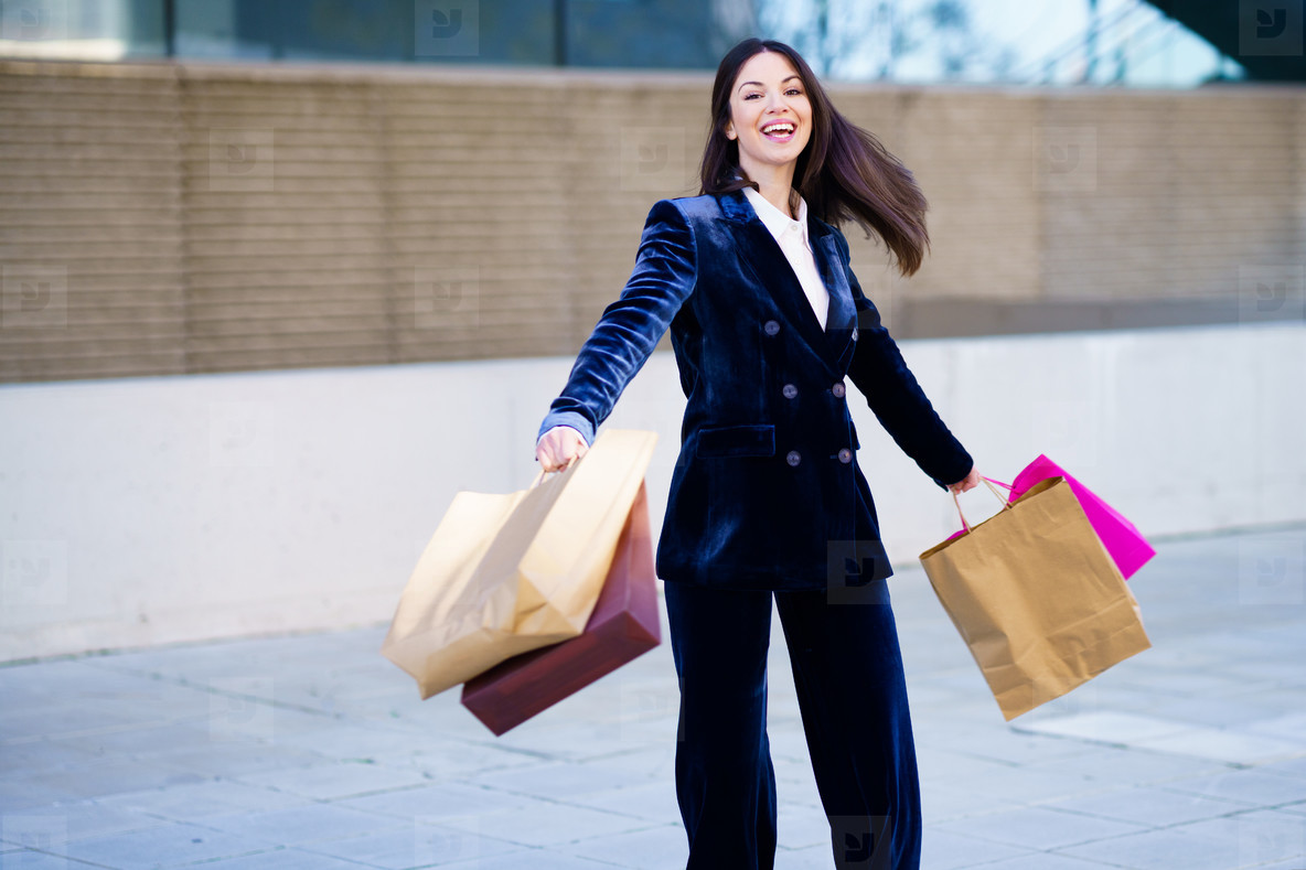 Caucasian woman turning with joy for her purchases in shopping bags