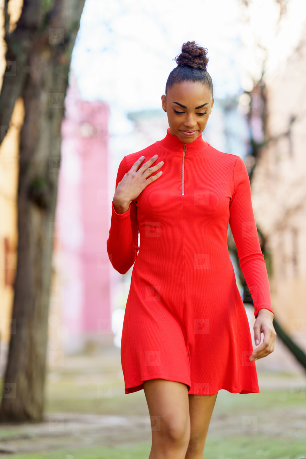 Smiling mixed woman in red dress walking down the street