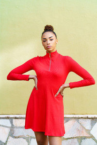 Young black woman in red dress with a serious expression in urban background
