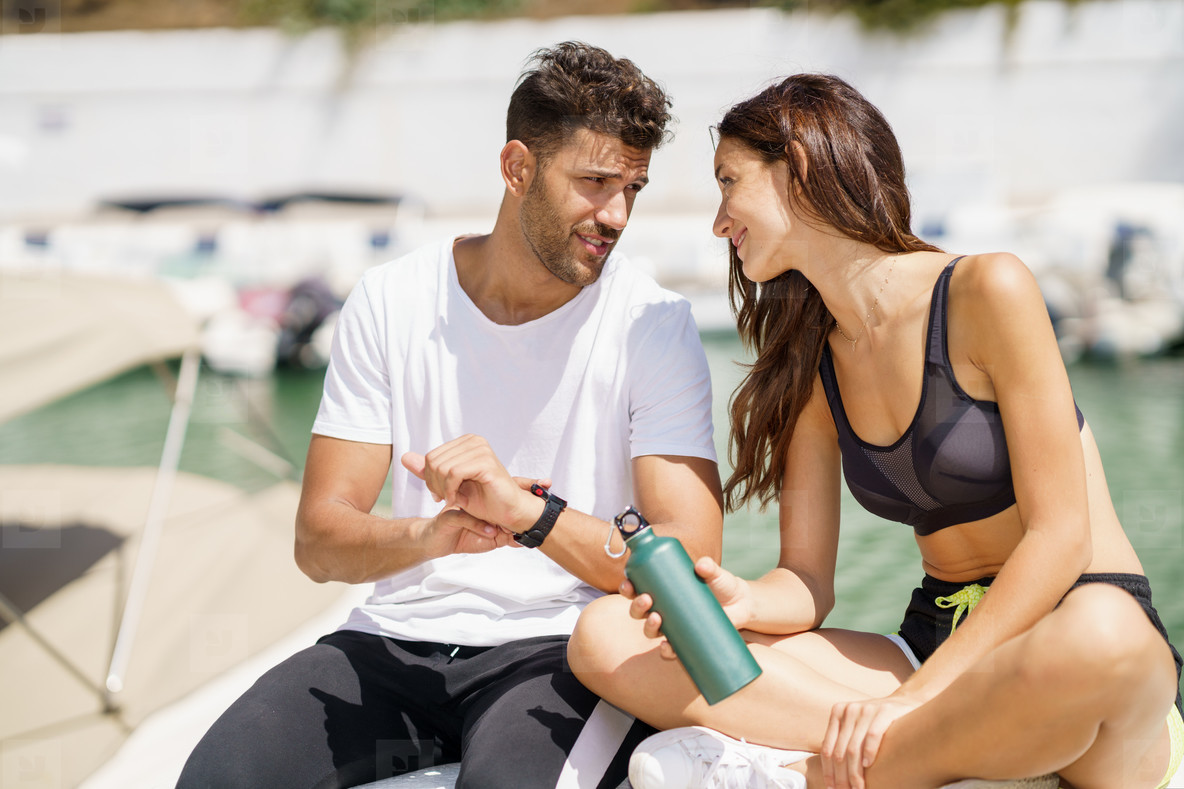 Man showing his marks to a woman on a sports watch after exercise  People using smartwatch