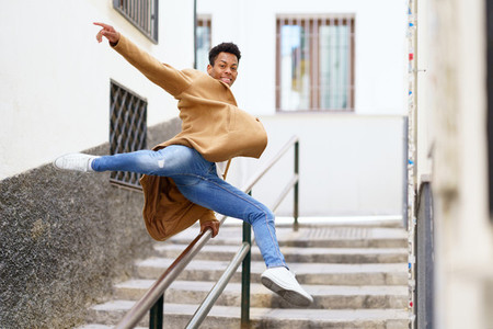 Cuban man jumping for joy over a handrail in the street