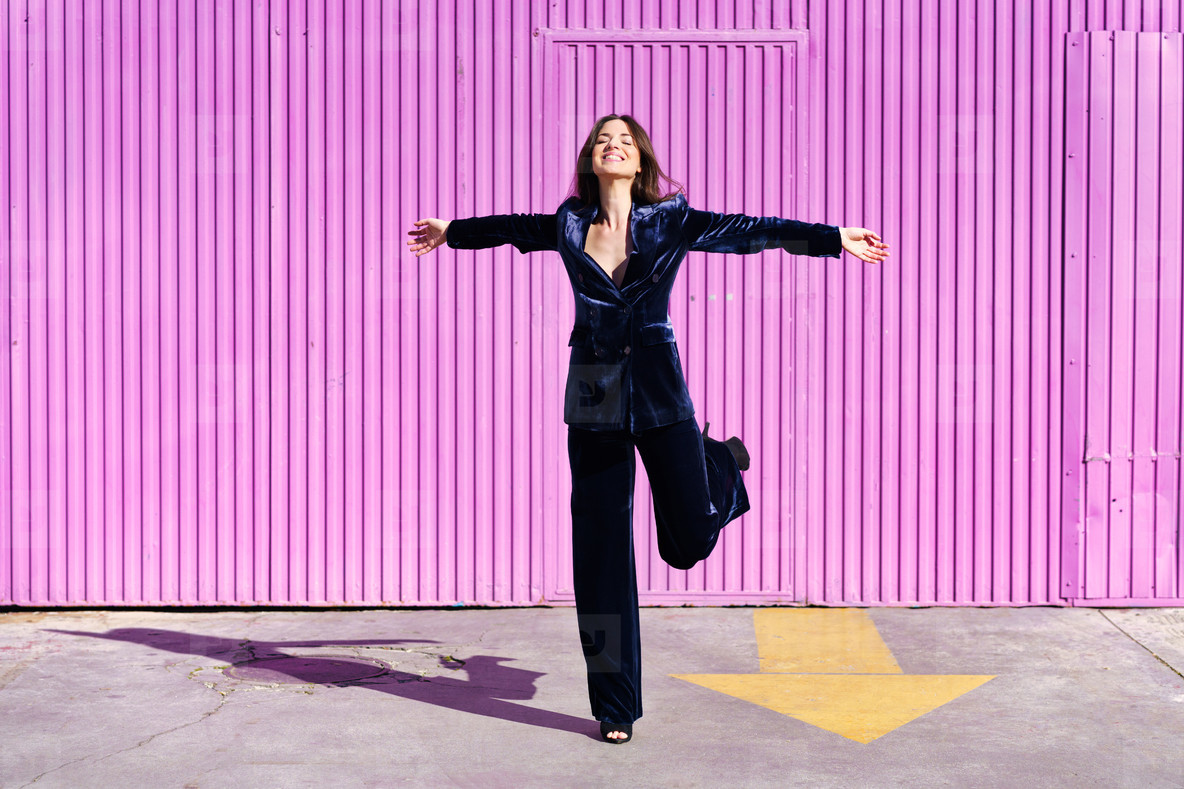 Woman wearing blue suit dancing near pink shutter