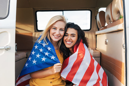 Two young female friends with American flag sitting in a camper van  Beautiful women with USA flag looking at camera