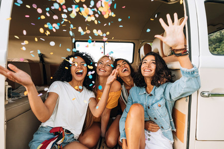 Women friends throwing confetti in the air while sitting in camper van